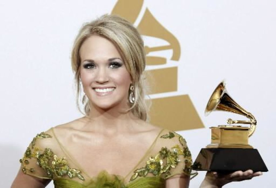 """Carrie  Underwood holds the best female country vocal performance award for """"Last Name"""" backstage at the 51st Annual Grammy Awards on Sunday, Feb. 8, 2009, in Los Angeles. (AP Photo/Matt Sayles)"""