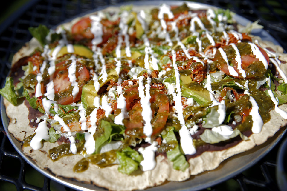 Photo -  One of Revolucion's vegetarian offerings is the Oaxacan Pizza — a crispy 10-inch corn tortilla topped with black beans, lettuce, tomato, avocado, crema, salsa verde and queso fresco. [Photo by Sarah Phipps, The Oklahoman]
