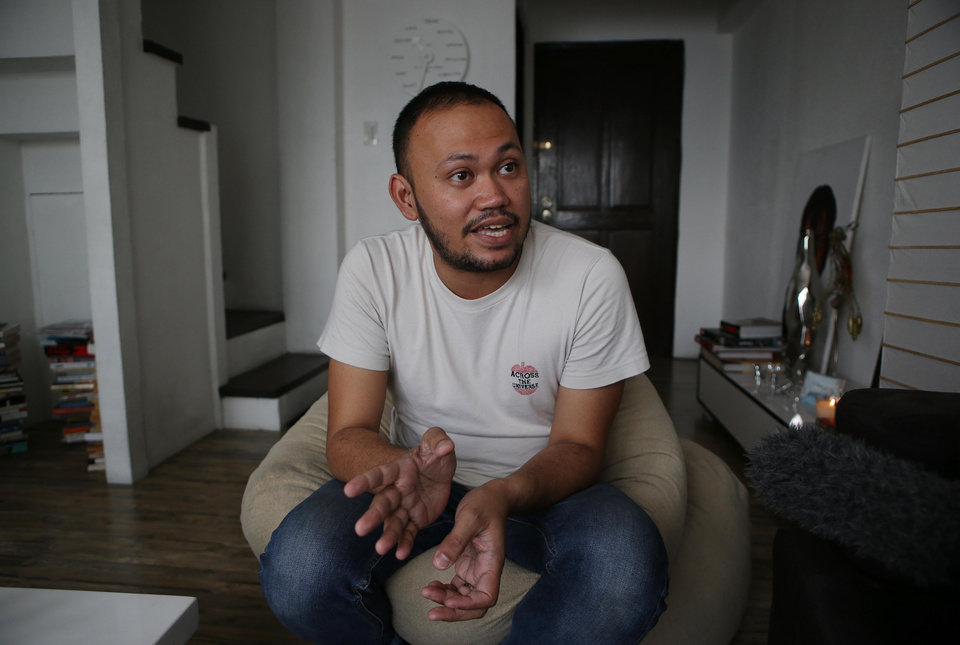 """In this photo taken on May 8, 2013, Filipino director Borinaga Alix Jr. talks during an interview inside his home in suburban Quezon city, north of Manila, Philippines. Alix could have shot his film """"Death March"""" on location in a large-scale production, but instead chose to film it in black-and-white and almost entirely inside a studio using hand-painted backdrops, with close-ups of actors' painted faces portraying their struggles with nightmares and hallucinations in one of the bloodiest episodes of World War II. (AP Photo/Aaron Favila)"""