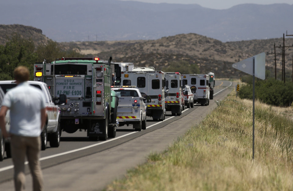 Photo - A procession of the vehicles left by the 19 elite Granite Mountain Hotshot crew members killed over the weekend are removed from the fire area near Yarnell, Ariz., Wednesday, July 3, 2013. Violent wind gusts on Sunday turned a small, lightning-ignited forest fire in the town into an out-of-control wildfire that left no escape for the team of Hotshots. (AP Photo/Chris Carlson)