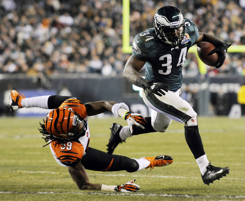 Philadelphia Eagles' Bryce Brown, right, breaks past Cincinnati Bengals' Emmanuel Lamur in the first half of an NFL football game, Thursday, Dec. 13, 2012, in Philadelphia. (AP Photo/Michael Perez)
