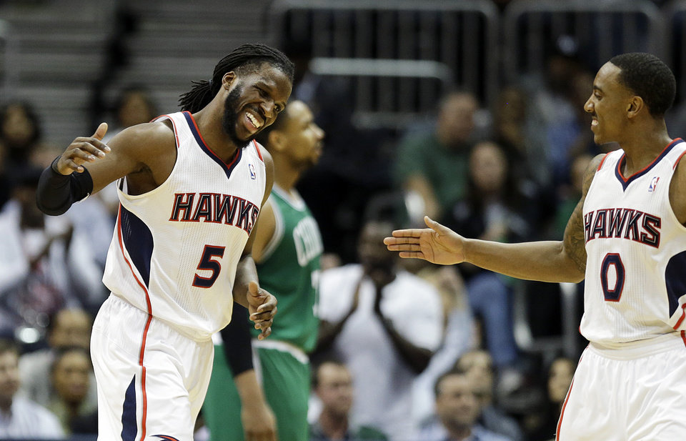 Photo - Atlanta Hawks' DeMarre Carroll, left, high-fives teammate Jeff Teague after scoring a basket in the fourth quarter of an NBA basketball game against the Boston Celtics, Wednesday, April 9, 2014, in Atlanta. Atlanta won 105-97. (AP Photo/David Goldman)