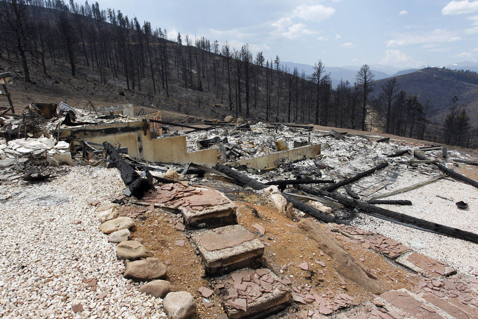 Photo - A home is left in rubble after being destroyed by the High Park Fire in the Glacier View residential area near Livermore, Colo., on Monday, July 2, 2012. The last evacuees from the fire in have been allowed to return home as crews fully contained the136-square-mile wildfire that killed one resident and destroyed 259 houses. (AP Photo/Ed Andrieski) ORG XMIT: COEA108
