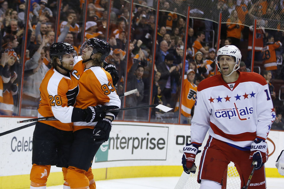 Photo - Philadelphia Flyers' Claude Giroux, left, celebrates with Jakub Voracek as Washington Capitals' Eric Fehr skates by after Giroux's goal during the second period of an NHL hockey game, Wednesday, March 5, 2014, in Philadelphia. (AP Photo/Matt Slocum)