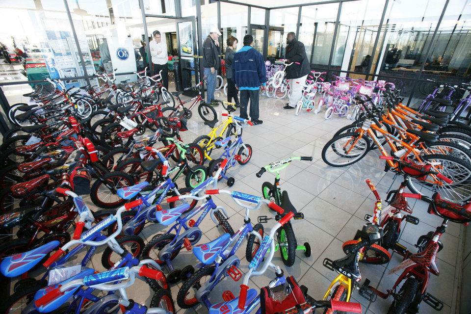 Photo - Bicycles fill an area of Hudiburg Chevrolet in Midwest City, as Hudiburg Auto Group handed out 100 bikes to military and National Guard parents to give their children for Christmas.Photo by PAUL HELLSTERN, The Oklahoman