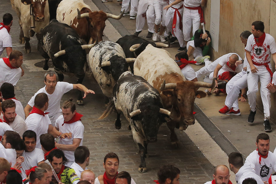 Photo - Revelers run along Torrestrella fighting bulls during the running of the bulls of the San Fermin festival, in Pamplona, Spain, Monday, July 7, 2014. Revelers from around the world arrive here to take part in the eight-day event glorified by Ernest Hemingway's 1926 novel