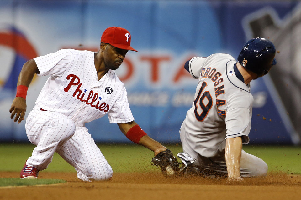 Photo - Houston Astros' Robbie Grossman, right, is tagged out by Philadelphia Phillies shortstop Jimmy Rollins after trying to steal second base during the fourth inning of an interleague baseball game, Tuesday, Aug. 5, 2014, in Philadelphia. (AP Photo/Matt Slocum)