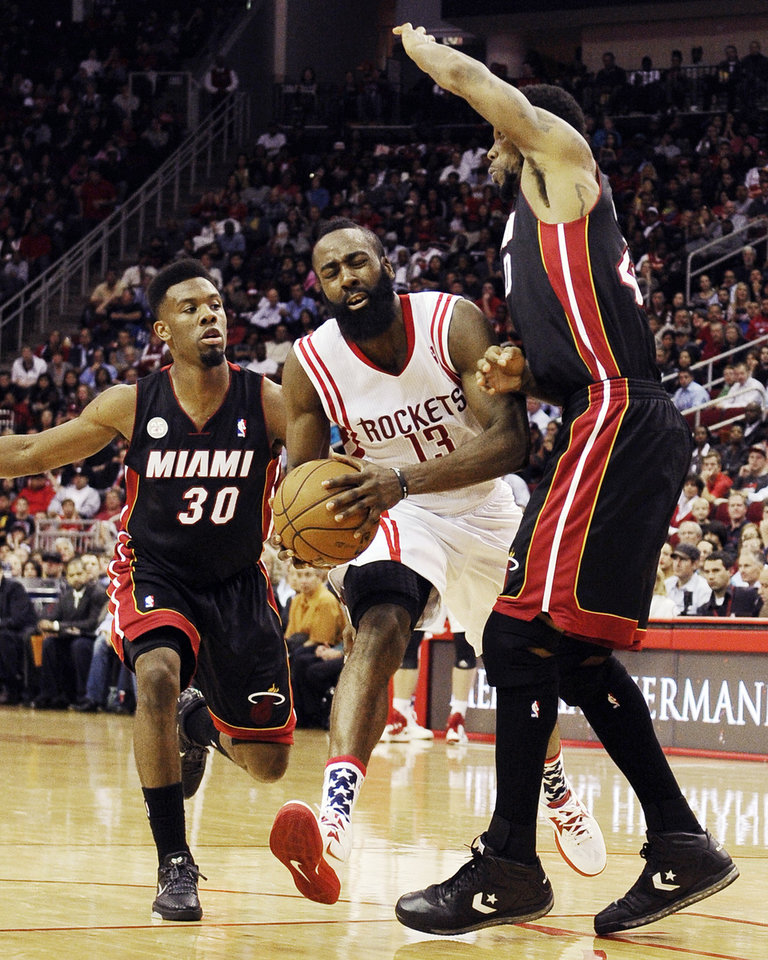 Photo -   Houston Rockets' James Harden (13) heads to the basket between Miami Heat's Norris Cole (30) and Udonis Haslem (40) in the second half of an NBA basketball game, Monday, Nov. 12, 2012, in Houston. The Heat won 113-110. (AP Photo/Pat Sullivan)