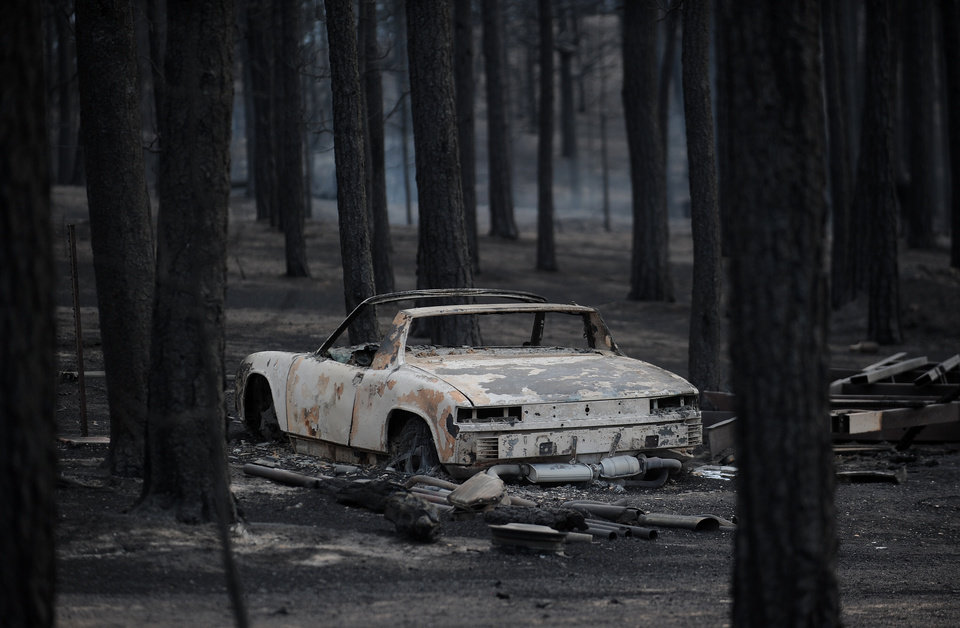 Photo - The remains of a vehicle stands among a burned out forest along Holmes Road Thursday, June 13, 2013, during the third day of the Black Forest Fire near Colorado Springs, Colo. (AP Photo/The Gazette, Christian Murdock) MAGS OUT