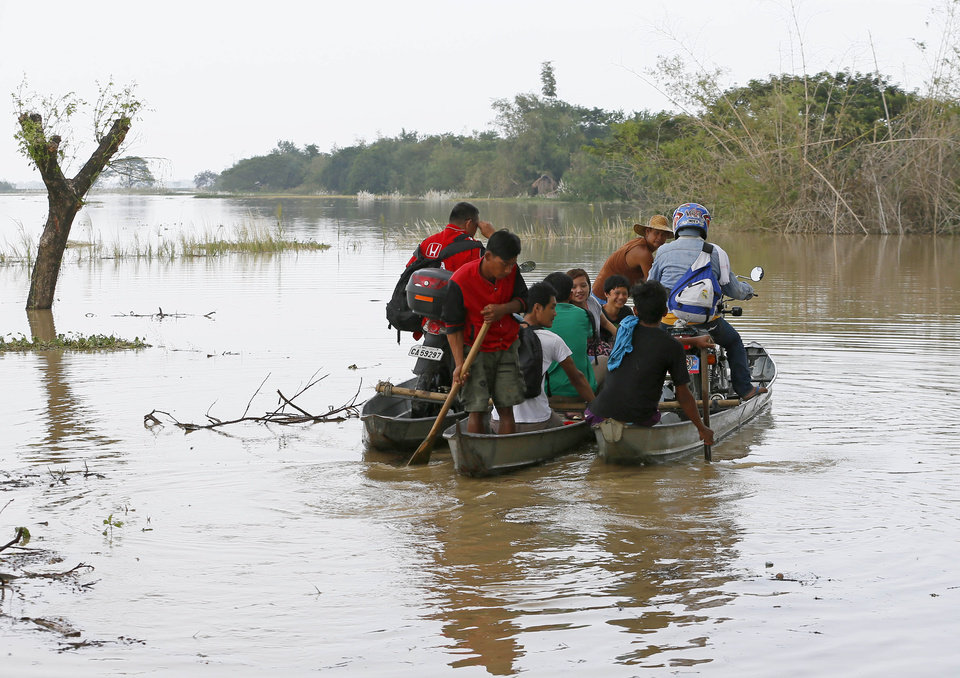 Photo - Commuters, who are unable to use the highway due to raging floodwaters, ride a boat to get to their destinations in La Paz township, Tarlac province, in northern Philippines Tuesday, Oct. 20, 2015. Slow-moving Typhoon Koppu blew ashore with fierce winds in the northeastern Philippines early Sunday, toppling trees and knocking out power and communications and forcing the evacuation of thousands of villagers. (AP Photo/Bullit Marquez)