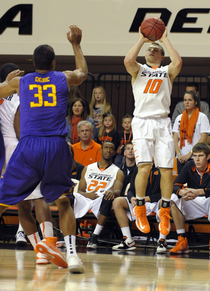 Photo - Oklahoma State guard Phil Forte, right, shoots over Tennessee Tech forward Dennis Ogbe, left, during the second half of an NCAA college basketball game in Stillwater, Okla., Saturday, Dec. 22, 2012. Forte scored 22 points in the 78-42 win over Tennessee Tech. (AP Photo/Brody Schmidt)