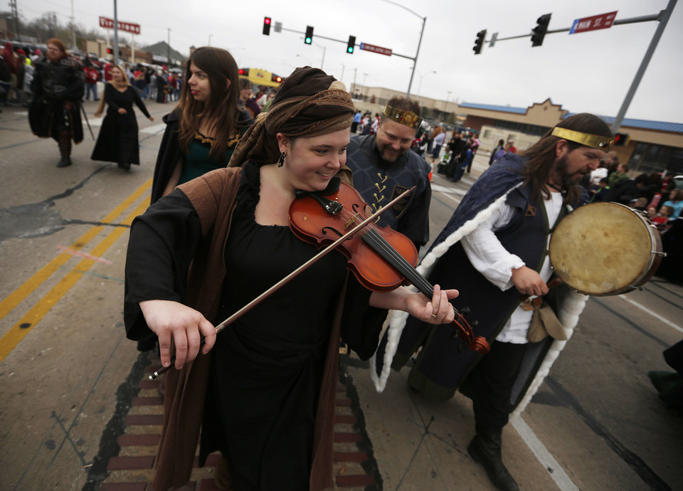 Denisa Wohnoutka and Robert Raymond play music as they walk in the Holiday Christmas Parade Saturday in downtown Norman.