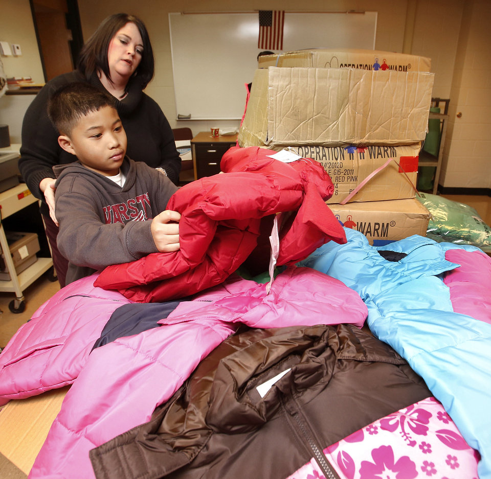 Teacher Jennifer Rader helps Joseph Nguyen, a second grader, select a coat that fits him Monday afternoon at Southern Hills Elementary. About 2,000 children in Oklahoma City Public Schools will receive new coats from a national nonprofit called Operation Warm. <strong>Jim Beckel - THE OKLAHOMAN</strong>