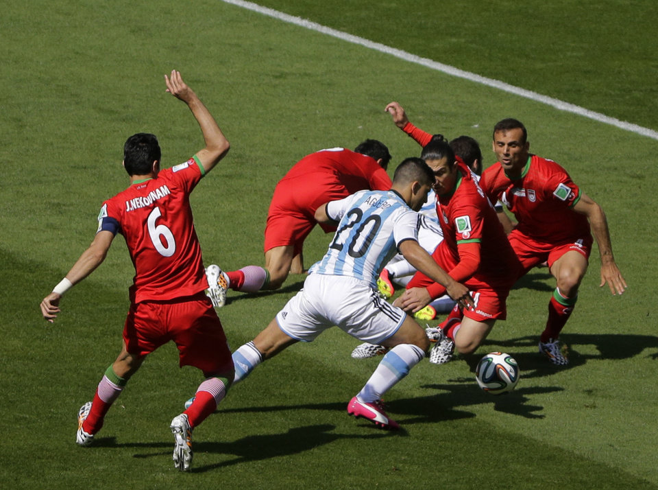 Photo - Argentina's Sergio Aguero, center, tries to take the ball through Iran's defense during the group F World Cup soccer match between Argentina and Iran at the Mineirao Stadium in Belo Horizonte, Brazil, Saturday, June 21, 2014. At left Iran's Javad Nekounam. (AP Photo/Sergei Grits)