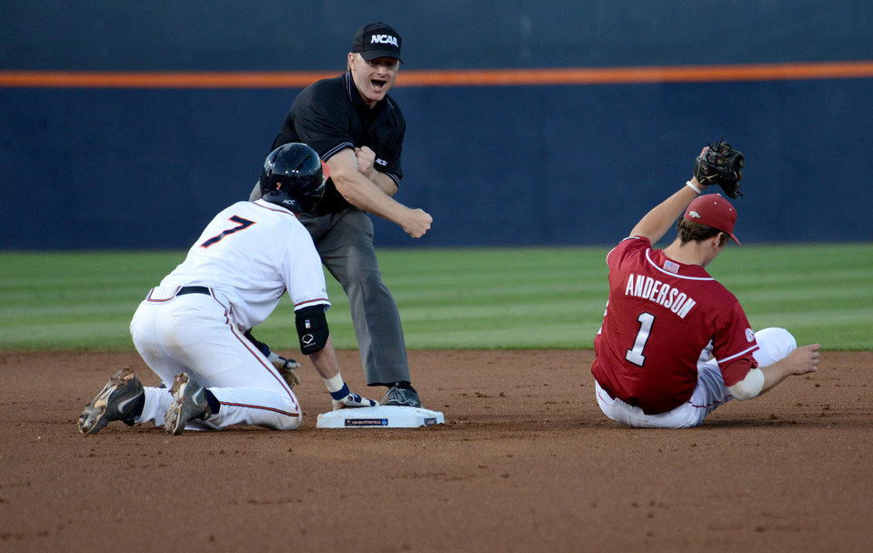 Photo - Virginia's Branden Cogswell, left, is called out as Arkansas' Brian Anderson holds the ball in his glove during the first inning of an NCAA college baseball regional tournament game in Charlottesville, Va., Saturday, May 31, 2014. (AP Photo/Pat Jarrett)