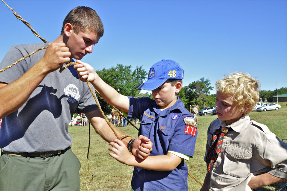Photo - Martin Gilligan, 16, teaches Miles Hulbert, 9, and Connor Cook, 9, how to tie a timber hitch. All three are from Edmond. There were attending a Webelos campout in southwest Oklahoma City. Photo by M. Tim Blake, for The Oklahoman