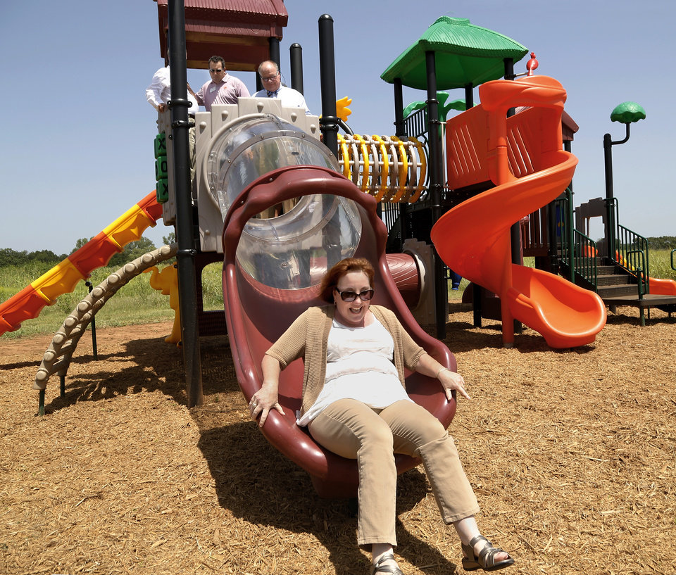 Photo -  Edmond city councilwoman Victoria Caldwell laughs as she lands at the bottom of an enclosed slide while testing the new playground equipment. Rotary Club members participated in the dedication of the playground equipment donated by the Rotary Club of Edmond at the new Edmond 66 Park on Wednesday. Photo by Jim Beckel, The Oklahoman   Jim Beckel -  THE OKLAHOMAN