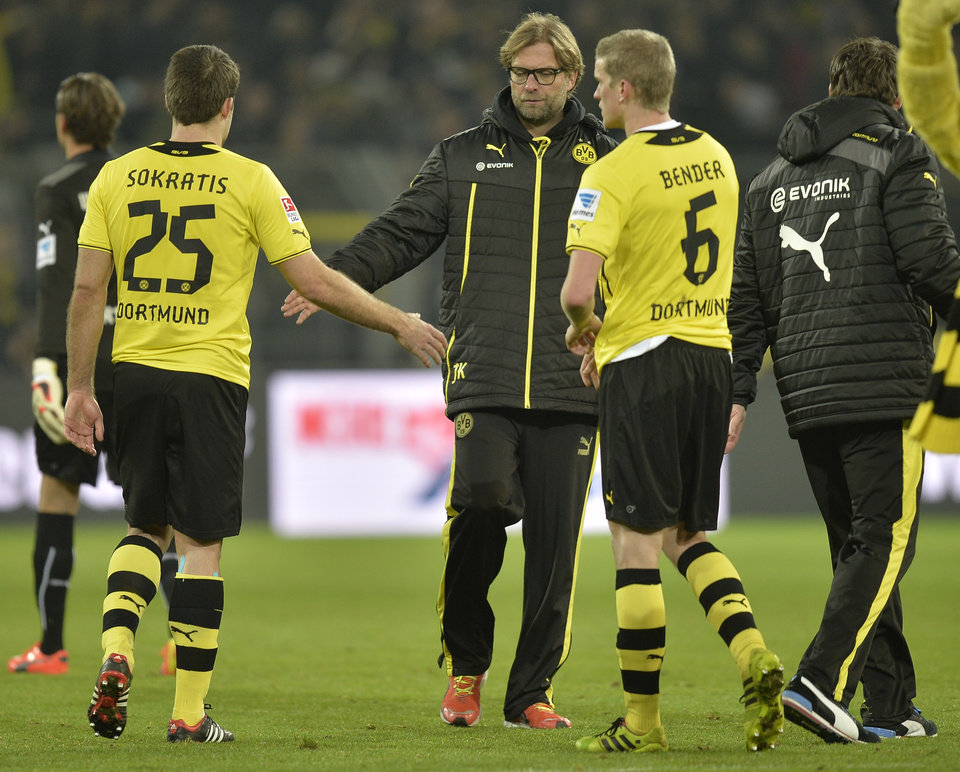 Photo - Dortmund head coach Juergen Klopp shakes hands with Sokratis, left, and Sven Bender, right, after the German Bundesliga soccer match between Borussia Dortmund and FC Augsburg in Dortmund,  Germany, Saturday, Jan. 25, 2014. The match ended 2-2.  (AP Photo/Martin Meissner)