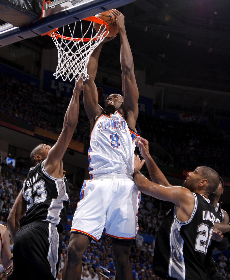 Photo - Oklahoma City's Serge Ibaka (9) dunks the ball between San Antonio's Boris Diaw (33) and Tim Duncan (21) during Game 4 of the Western Conference Finals between the Oklahoma City Thunder and the San Antonio Spurs in the NBA playoffs at the Chesapeake Energy Arena in Oklahoma City, Saturday, June 2, 2012. Photo by Bryan Terry, The Oklahoman