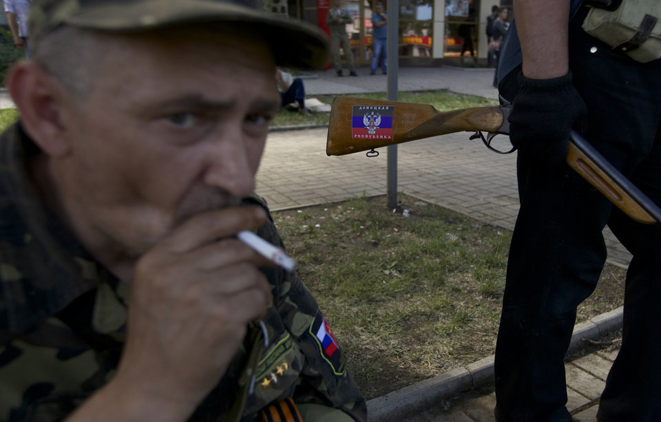 Photo - A sticker with Donetsk people's republic colors is seen on the hunting rifle of a local man who came to a check point on a road leading to the airport, in Donetsk, Ukraine, on Tuesday, May 27, 2014.  The eastern city of Donetsk was in turmoil Tuesday a day after government forces used fighter jets to stop pro-Russian militia from taking over the airport. Dozens were reported killed and the mayor went on television to urge residents to stay indoors. (AP Photo/Ivan Sekretarev)