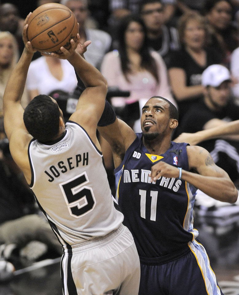 Photo - San Antonio Spurs' Cory Joseph, left, shoots over Memphis Grizzlies' Mike Conley during the first half of Game 1 of the Western Conference final NBA basketball playoff series Sunday, May 19, 2013, in San Antonio. (AP Photo/Darren Abate)