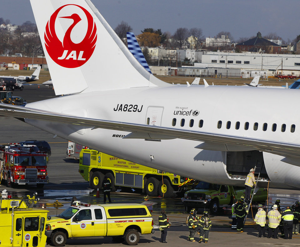 Photo - FILE - In this Jan. 7, 2013, file photo, a Japan Airlines Boeing 787 jet aircraft is surrounded by emergency vehicles while parked at a terminal E gate at Logan International Airport in Boston as a fire chief looks into the cargo hold. The FAA failed to properly test the Boeing 787's lithium-ion batteries and relied too much on Boeing for technical expertise, a new report from the National Transportation Safety Board says Thursday, May 22, 2014. (AP Photo/Stephan Savoia, File)