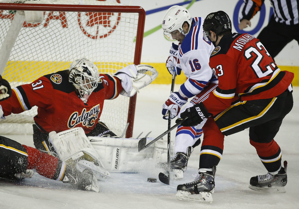 Photo - New York Rangers' Derick Brassard, center, tries to get the puck past Calgary Flames goalie Karri Ramo, from Finland, as Flames' Sean Monahan defends during the first period of an NHL hockey game in Calgary, Alberta, Friday, March 28, 2014. (AP Photo/The Canadian Press, Jeff McIntosh)