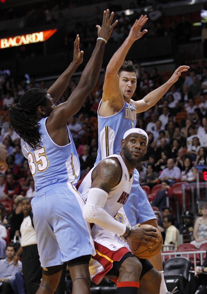 Photo -   Miami Heat forward LeBron James, center, looks for an opening past Denver Nuggets forwards Kenneth Faried (35) and Danilo Gallinari, rear, during the first half of an NBA basketball game, Saturday, Nov. 3, 2012 in Miami. (AP Photo/Wilfredo Lee)
