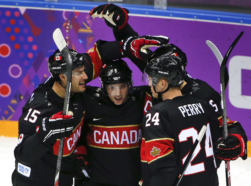 Photo - Team Canada celebrates a first period goal against Austria during a men's ice hockey game at the 2014 Winter Olympics, Friday, Feb. 14, 2014, in Sochi, Russia. (AP Photo/Julio Cortez)