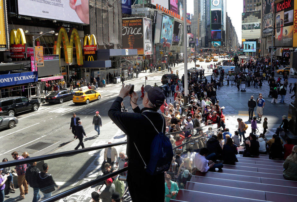 Photo - A man takes a photo in New York's Times Square, Thursday, April 25, 2013. The Boston Marathon bombing suspects had planned to blow up their remaining explosives in New York's Times Square, officials said Thursday. (AP Photo/Richard Drew)