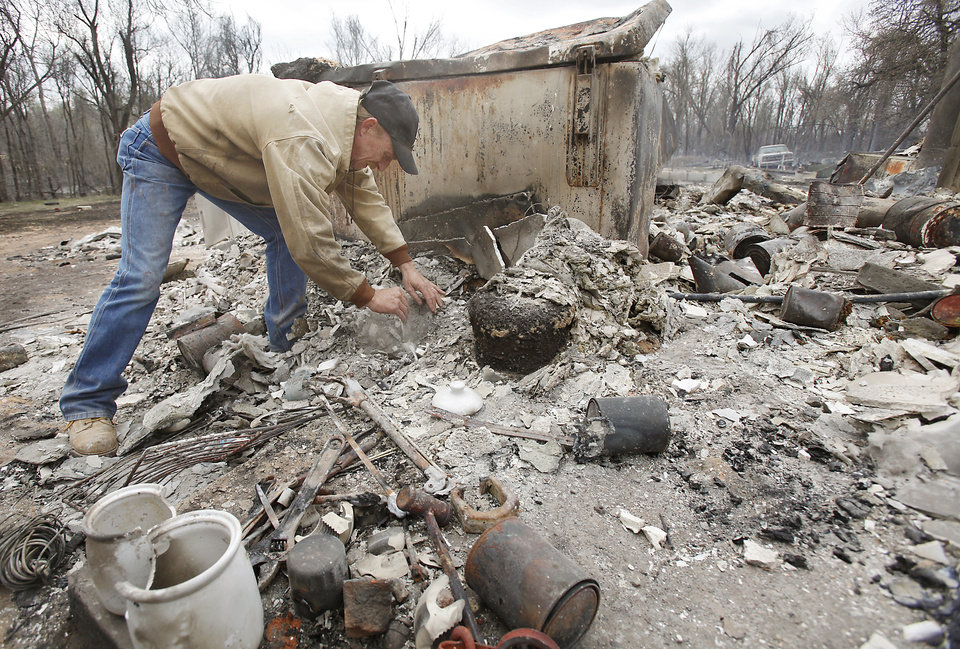 Photo - Kenneth Wertz dig through the remains of his house of more than 40 years as he looks for a few salvageable remains from the house that was destroyed by wildfires on Friday, April 10, 2009, in Choctaw, Okla.  Photo by Chris Landsberger, The Oklahoman
