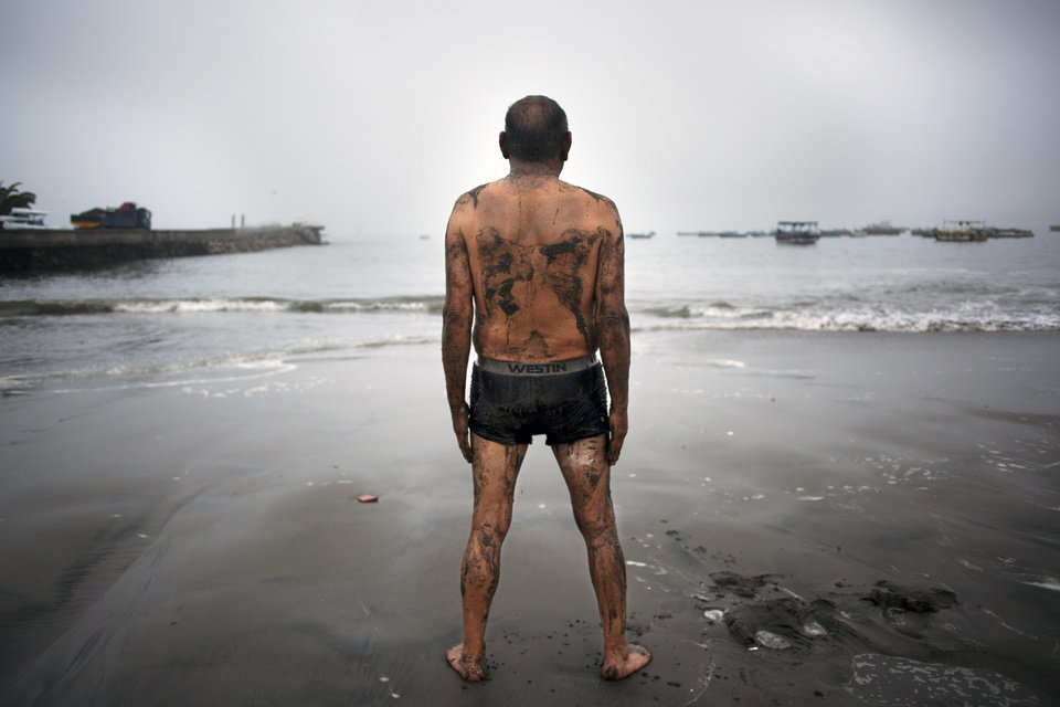 Photo - Teodocio Perez, 71, covered with a thin layer of wet sand, looks out at the Pacific Ocean during his morning exercises on the Playa de Pescadores shore in Lima, Peru, Wednesday, April 2, 2014.  Chilean authorities discovered surprisingly light damage Wednesday from a magnitude-8.2 quake that struck in the Pacific Ocean, Tuesday evening, near the mining port of Iquique, about 87 miles from the Peruvian border. Tsunami warnings issued for Chile, Peru and Ecuador have been lifted. Six deaths have been reported. (AP Photo/Rodrigo Abd)