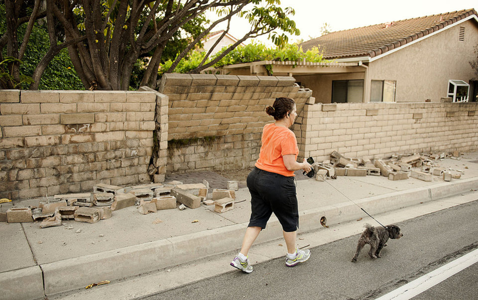 Photo - A woman walks her dog past a broken block wall in Fullerton, Calif., on Saturday, March 29, 2014,  after an earthquake hit Orange County Friday night. More than 100 aftershocks have rattled Orange County south of Los Angeles where a magnitude-5.1 earthquake struck Friday.  Despite the relatively minor damage, no injuries have been reported. (AP Photo/The Orange County Register, Ken Steinhardt)   MAGS OUT; LOS ANGELES TIMES OUT