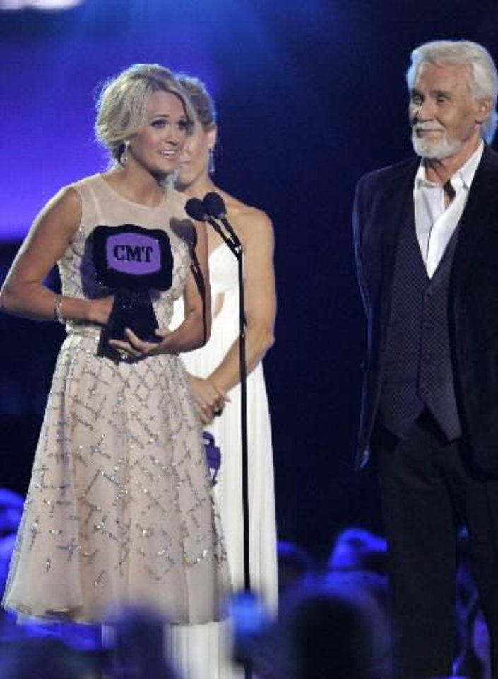 "Checotah native Carrie Underwood, left, accepts the award for video of the year for ""Blown Away"" at the 2013 CMT Music Awards at Bridgestone Arena on Wednesday, June 5, 2013, in Nashville, Tenn. Looking on at right is presenter Kenny Rogers. (AP)"