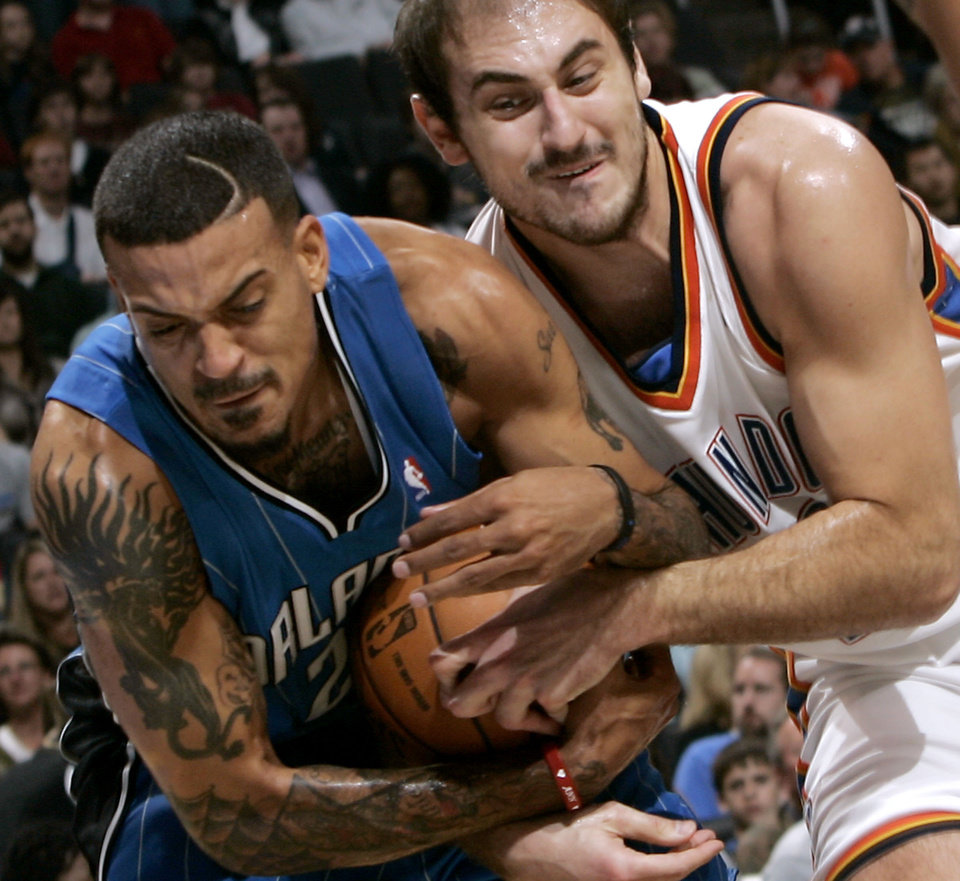 Photo - Oklahoma City's Nenad Krstic and Orlando's Matt Barnes battle for a loose ball during the NBA basketball game between the Orlando Magic and the Oklahoma City Thunder at the Ford Center in Oklahoma City, on Sunday, Nov. 8, 2009. By John Clanton, The Oklahoman