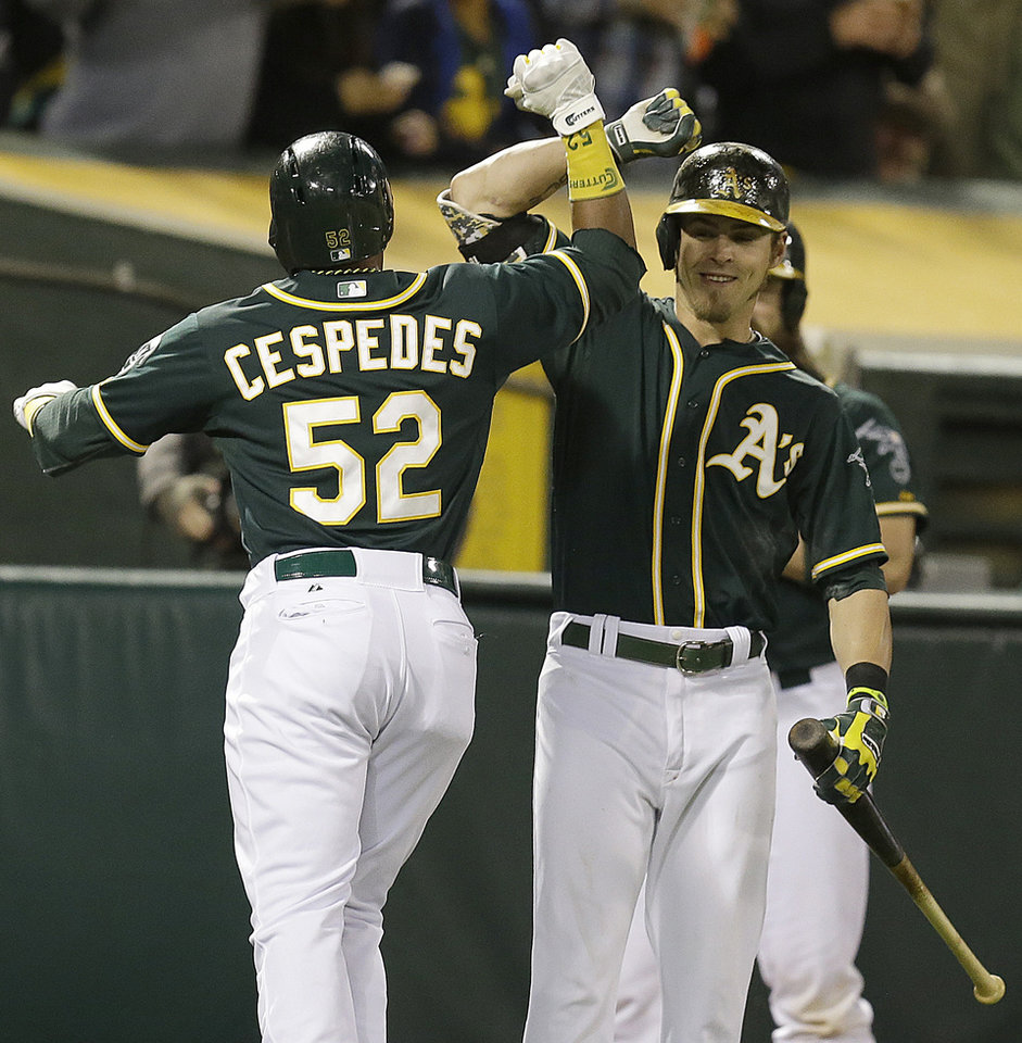 Photo - Oakland Athletics' Yoenis Cespedes (52) is congratulated by Josh Reddick, right, after Cespedes hit a home run off Washington Nationals' Doug Fister in the fifth inning of a baseball game on Friday, May 9, 2014, in Oakland, Calif. (AP Photo/Ben Margot)
