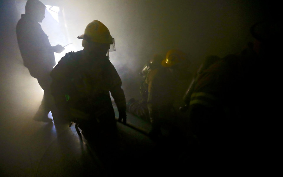 Photo - Edmond firefighters make their way through a smoke-filled building in downtown as part of a self-contained breathing apparatus drill. PHOTO BY CHRIS LANDSBERGER, THE OKLAHOMAN.  CHRIS LANDSBERGER - THE OKLAHOMAN