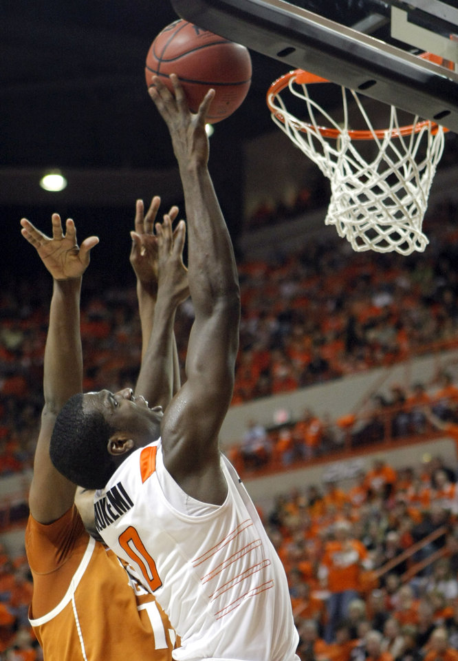 Photo - Oklahoma State's Jean-Paul Olukemi (0) shoots in front of Texas' Tristan Thompson (13) during the basketball game between Oklahoma State and Texas, Wednesday, Jan. 26, 2011, at Gallagher-Iba Arena in Stillwater, Okla. Photo by Sarah Phipps, The Oklahoman ORG XMIT: KOD