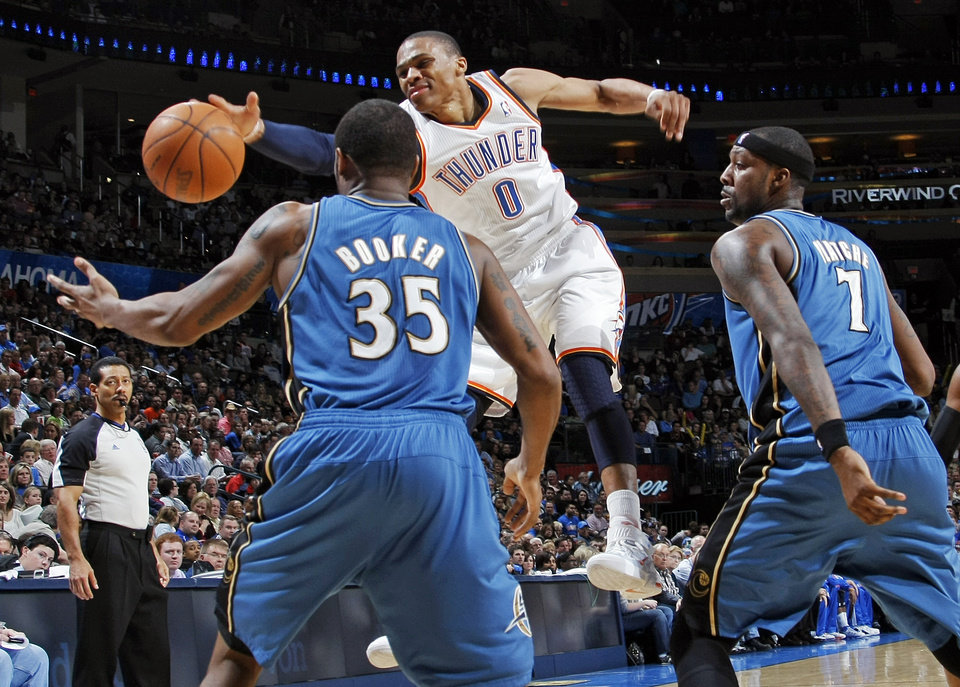 Photo - Oklahoma City's Russell Westbrook (0) tries to keep control of the ball between Trevor Booker (35) and Andray Blatche (7) of Washington during the NBA basketball game between the Washington Wizards and the Oklahoma City Thunder at the Oklahoma City Arena in Oklahoma City, Friday, January 28, 2011. The Thunder won, 124-117, in double overtime. Photo by Nate Billings, The Oklahoman