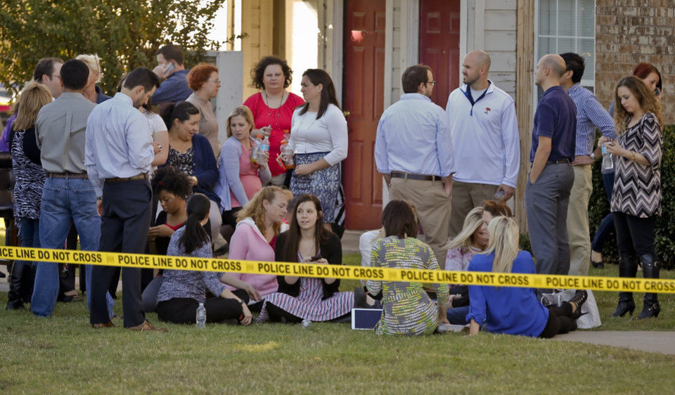 Photo - Workers from a nearby office building wait behind police lines at the Apple Creek Apartments near the scene of a hostage situation at Nextep in Norman Monday, Nov. 10, 2014.  in Norman, Okla. on Monday, Nov. 10, 2014.  Photo by Chris Landsberger, The Oklahoman