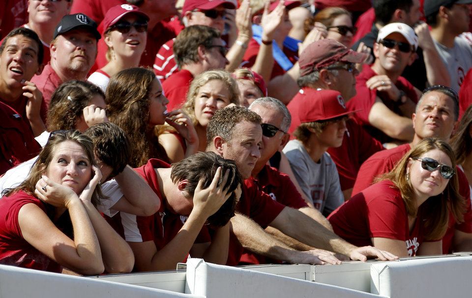 Photo - OU fans react during the Red River Rivalry college football game between the University of Oklahoma Sooners and the University of Texas Longhorns at the Cotton Bowl Stadium in Dallas, Saturday, Oct. 12, 2013. Texas won 36-20. Photo by Bryan Terry, The Oklahoman