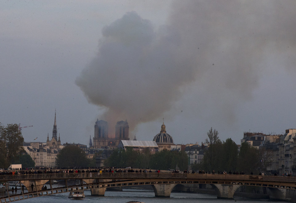Photo - Flames and plumes of smoke rise from Notre Dame cathedral as it burns in Paris, Monday, April 15, 2019. Massive plumes of yellow brown smoke is filling the air above Notre Dame Cathedral and ash is falling on tourists and others around the island that marks the center of Paris. (AP Photo/Michel Euler)