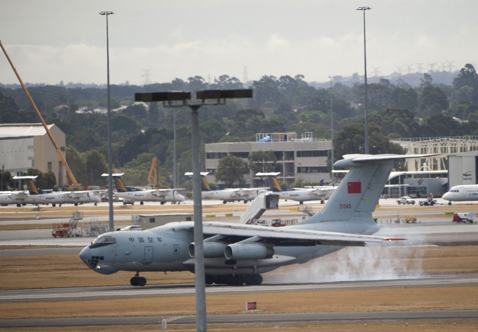 Photo - In this photo released by China's Xinhua news agency, a Chinese IL-76 plane searching for the missing Malaysia Airlines Flight MH370 lands at Perth airport, Australia, after a hunting sortie Monday, March 24, 2014. A Chinese plane on Monday spotted two white, square-shaped objects in an area identified by satellite imagery as containing possible debris from the missing Malaysian airliner, while the United States separately prepared to send a specialized device that can locate black boxes. The crew aboard an IL-76 plane sighted the object in the southern Indian Ocean and reported the coordinates to the Australian command center, which is coordinating the multinational search, as well as the Chinese icebreaker Snow Dragon, which is en route to the area, China's Xinhua News Agency reported. (AP Photo/Xinhua, Lui Siu Wai) NO SALES