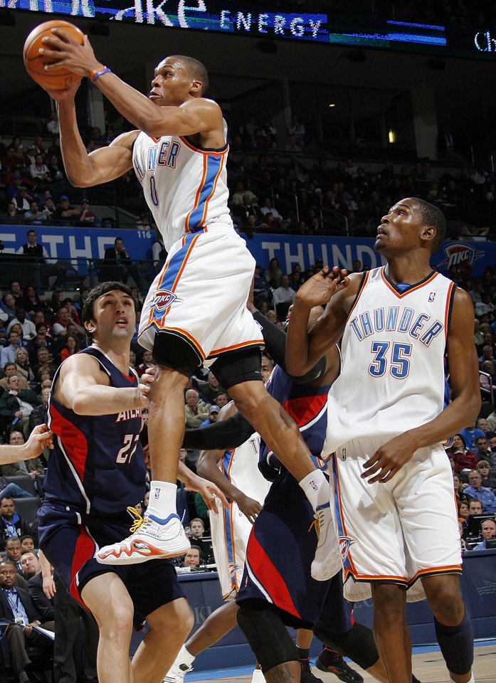 Oklahoma City\'s Russell Westbrook (0) moves to the hoop past Zaza Pachulia (27) of Atlanta as Oklahoma City\'s Kevin Durant (35) looks on during the NBA basketball game between the Atlanta Hawks and the Oklahoma City Thunder at the Ford Center in Oklahoma City, Tuesday, February 2, 2010. The Thunder won, 106-99. Photo by Nate Billings, The Oklahoman