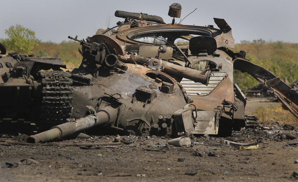 Photo - Part of a column of destroyed Ukrainian military vehicles are strewn near the village of Novokaterynivka, eastern Ukraine, Tuesday, Sept. 2, 2014. Ukrainian troops have over the past week suffered a string of major military losses in their offensive against Russian-backed separatist rebels, losing large swathes of territory and having hundreds of soldiers captured. (AP Photo/Sergei Grits)