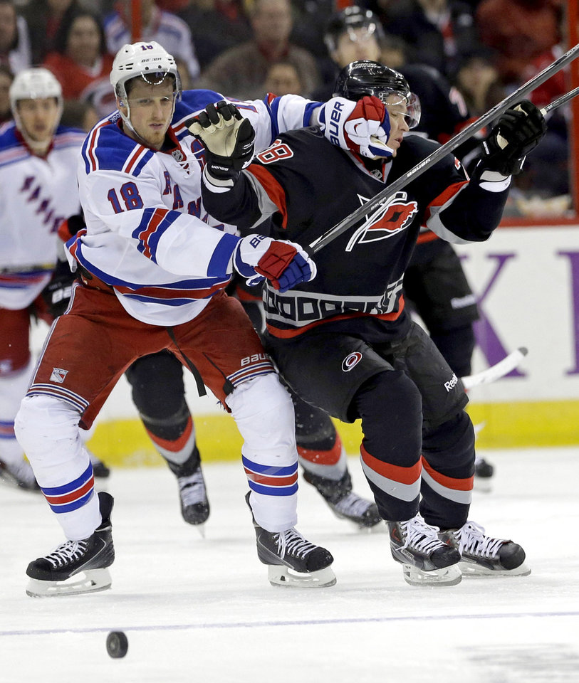 Photo - New York Rangers' Marc Staal (18) and Carolina Hurricanes' Alexander Semin (28) chase the puck during the second period of an NHL hockey game in Raleigh, N.C., Friday, March 7, 2014. (AP Photo/Gerry Broome)