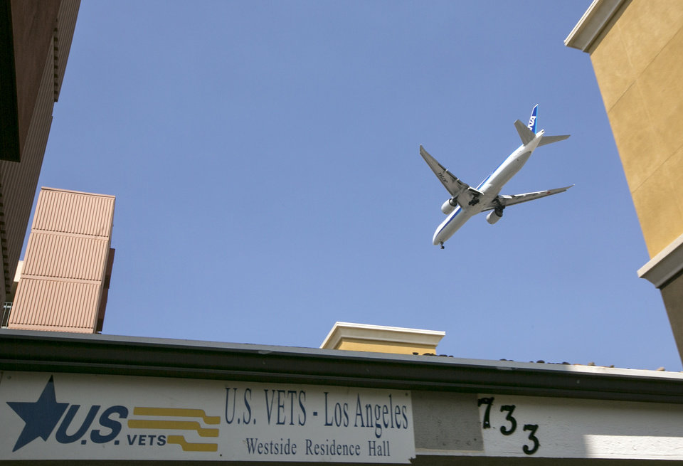 Photo - A jet pasts the main entrance of the U.S. Vets Los Angeles Westside Residences in Inglewood, Calif., Wednesday, Sept. 11, 2013.  A Los Angeles International Airport security screener Nna Alpha Onuoha, 29, was arrested hours after quitting his job for making unspecified threats referencing Wednesday's Sept. 11 anniversary and calling airport officials and telling them to evacuate terminals, the FBI said. Onuoha's apartment at the Westside Residences near LAX, found no dangerous materials but did turn up a note containing unspecified threats that cited the anniversary of the Sept. 11, 2001, attacks, authorities said. (AP Photo/Damian Dovarganes)
