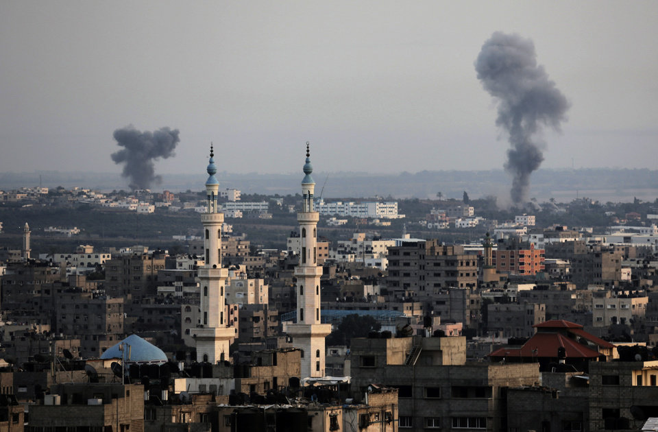 Photo - Columns of smoke rise following Israeli strikes on Gaza Strip, Saturday, July 12, 2014. Israeli airstrikes on Gaza hit a mosque and a center for the disabled where a few women were killed Saturday, raising the Palestinian death toll from the offensive to more than 130, Palestinian officials said, in an offensive that showed no signs of slowing down. (AP Photo/Adel Hana)