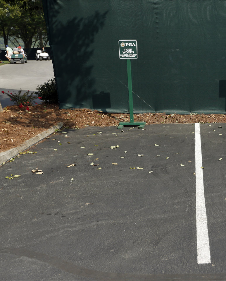 Photo - Tiger Woods' parking spot remains empty for the PGA Championship golf tournament at Valhalla Golf Club on Wednesday, Aug. 6, 2014, in Louisville, Ky. The tournament is set to begin on Thursday. (AP Photo/Mike Groll)