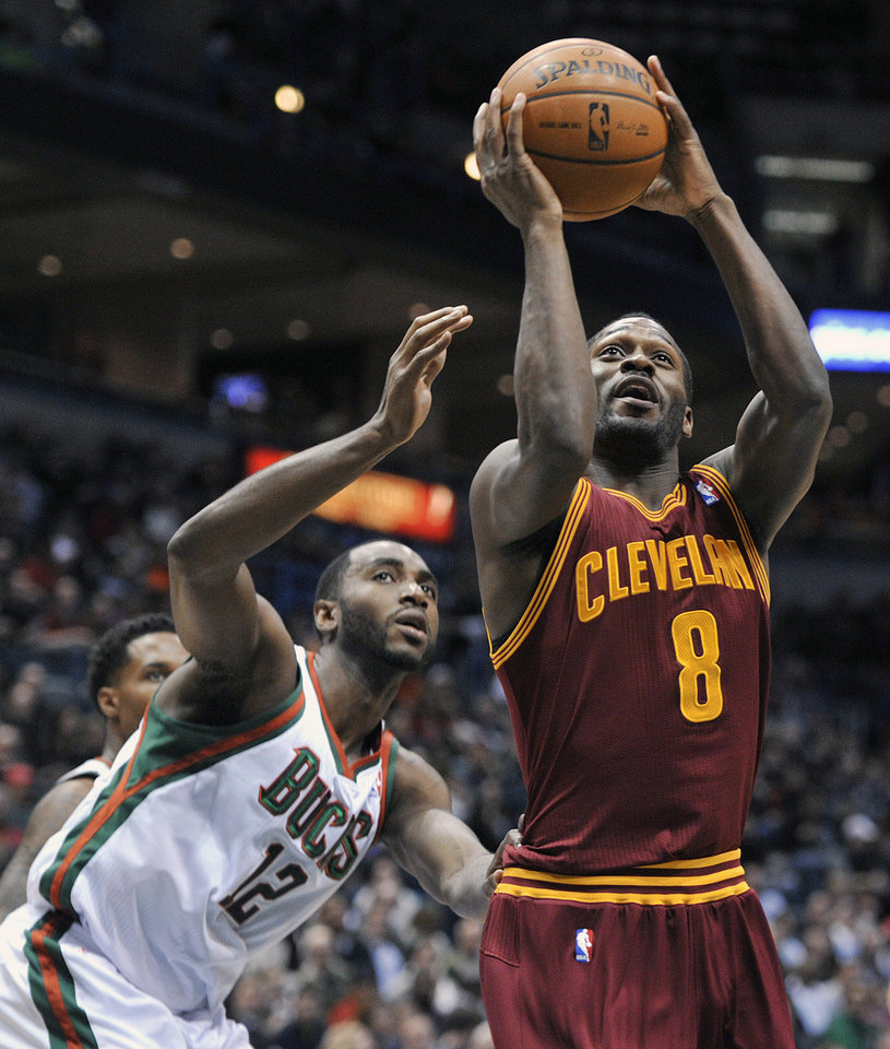 Photo - Milwaukee Bucks' Luc Richard Mbah a Moute (12) defends as Cleveland Cavaliers' Jeremy Pargo (8) shoots during the first half of an NBA basketball game Saturday, Dec. 22, 2012, in Milwaukee. (AP Photo/Jim Prisching)